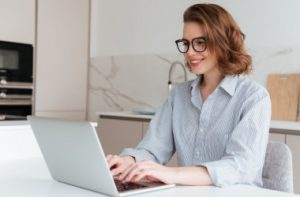 1-elegant-smiling-woman-in-glasses-and-striped-shirt-using-laptop-computer-while-siting-at-table-in-kitchen_171337-13030_i