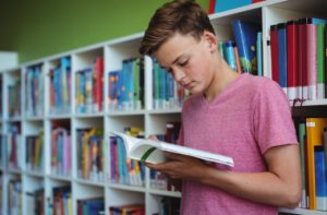 attentive-schoolboy-reading-book-library_i