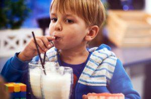 cute-cheerful-blond-boy-drinks-milk-cafe_i
